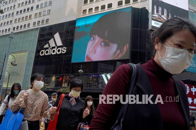 Orang-orang berjalan melewati toko pakaian olahraga Adidas di Hong Kong, Sabtu (27/3). H&M menghilang dari internet di China ketika pemerintah meningkatkan tekanan pada merek sepatu dan pakaian dan mengumumkan sanksi pada hari Jumat (26/3), terhadap pejabat Inggris dalam sebuah pertengkaran yang meningkat atas keluhan pelanggaran di wilayah Xinjiang.