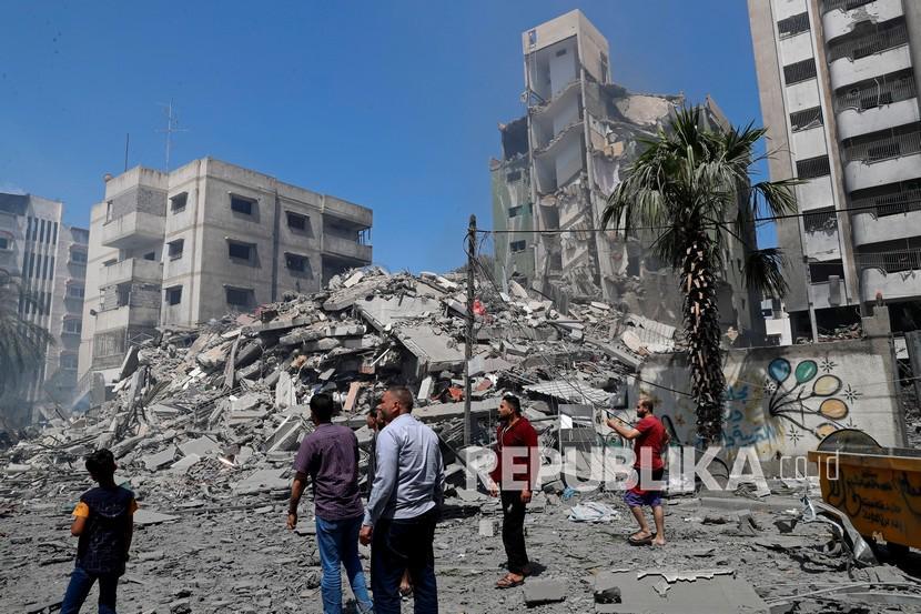 Orang-orang melihat puing-puing bangunan perumahan Yazegi yang dihancurkan oleh serangan udara Israel, di Kota Gaza, Ahad (16/5).