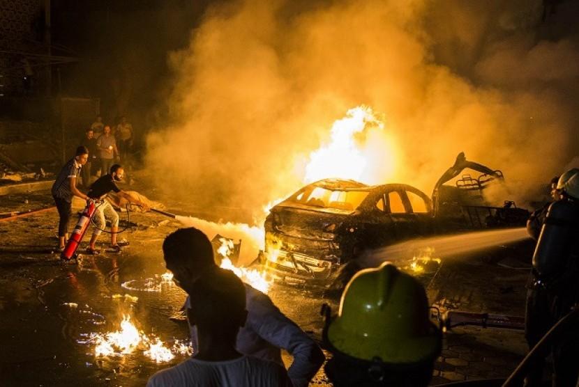 Orang-orang memadamkan api dari ledakan di dekat Pusat Kanker Nasional, Kairo, Mesir.