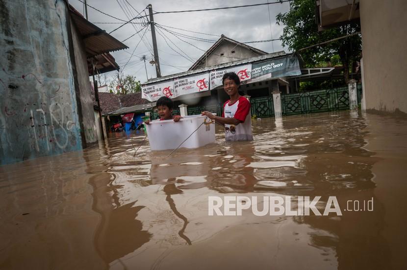 Orangtua mengevakuasi anaknya saat banjir di Rangkasbitung, Lebak, Banten, Selasa (14/9/2021). Tingginya intensitas hujan yang terjadi sejak Senin (13/9/2021) malam, menyebabkan ratusan rumah di Rangkasbitung terendam banjir setinggi dua meter.