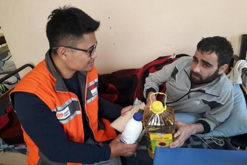 Overseas Department Head Rumah Zakat Joko Pamungkas bercakap-cakap dan memberikan bantuan paket makanan kepada pengungsi Suriah yang terluka akibat perang, Selasa (18/4).