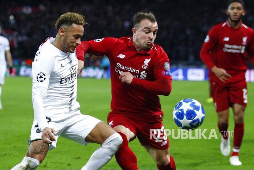 Striker PSG Neymar berebut bola dengan Xherdan Shaqiri pada laga Grup C Liga Champions antara Paris Saint Germain melawan Liverpool di stadion Parc des Princes, Paris, Kamis (29/11) dini hari.