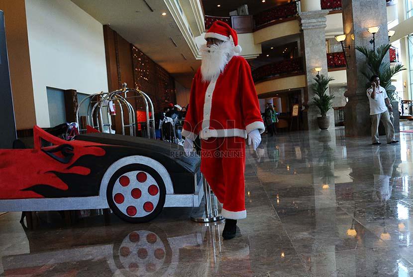 Pakaian Pekerja Pekerja mengenakan pakaian atribut natal pada salah satu Hotel di Jakarta, Senin (15/12)