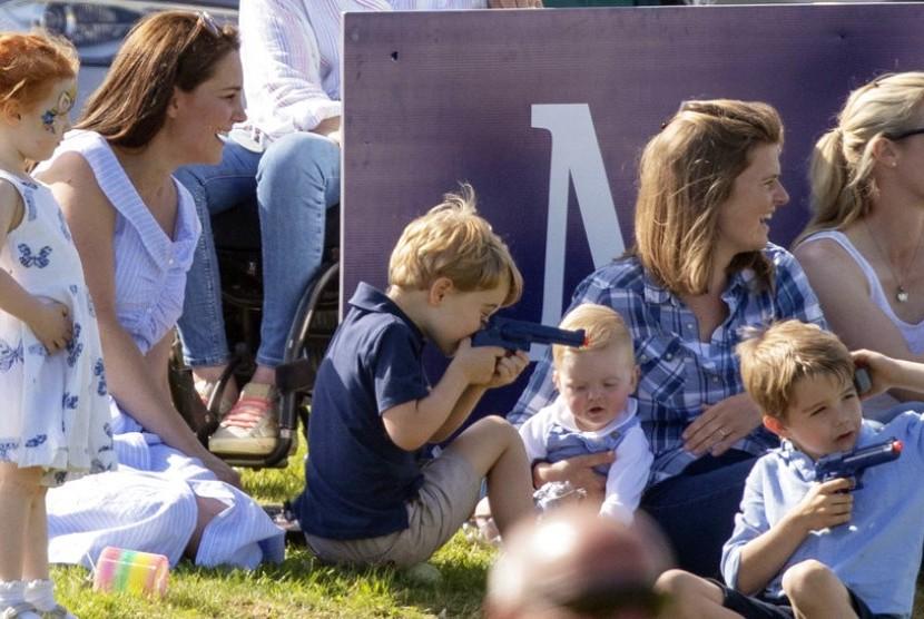 Pangeran George memegang mainan pistol-pistolan ditemani ibunya Kate Middleton, saat menyaksikan pertandingan polo Pangeran William.