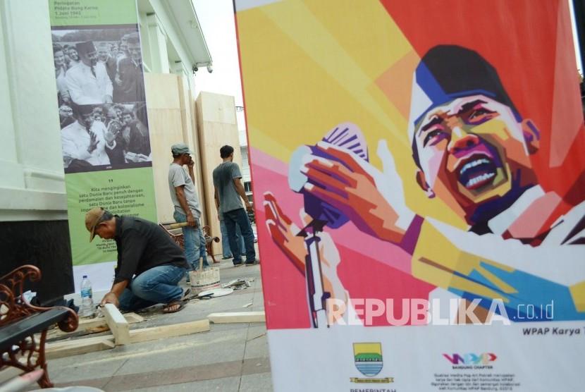 Para pekerja memasang gambar-gambar Presiden pertama RI Sukarno.