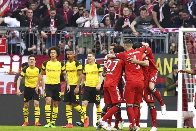 Para pemain Bayern Muenchen merayakan gol pembuka laga Bundesliga melawan Borussia Dortmund di Allianz Arena, Sabtu (6/4). Muenchen menang telak 5-0.