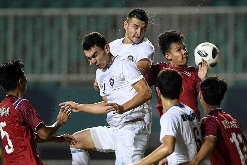 Para pemain Thailand berebut bola dengan Uzbekistan pada laga Grup B sepak bola putra Asian Games 2018, Ahad (19/8).