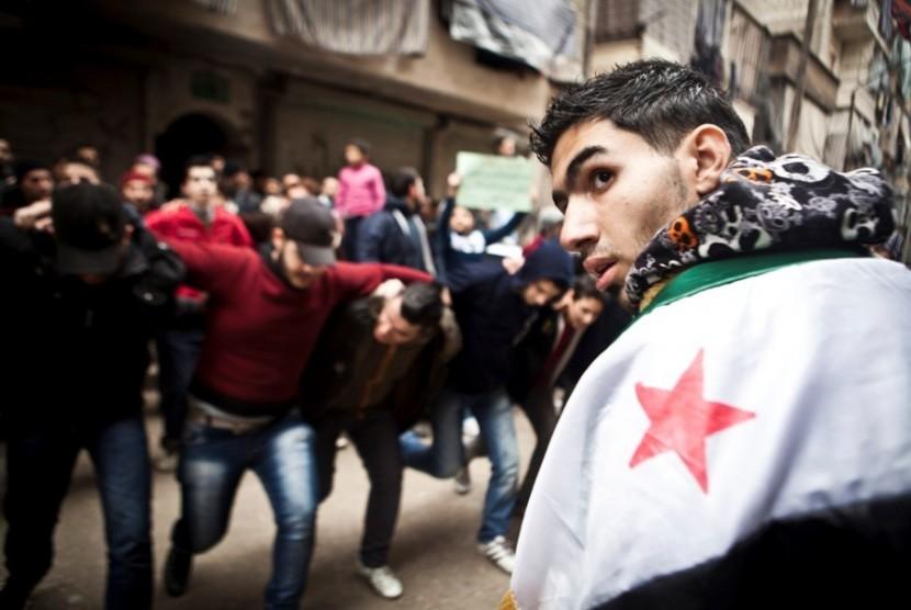 Para pemrotes menari dan meneriakkan slogan-slogan anti-Assad di Kota Aleppo, Suriah.