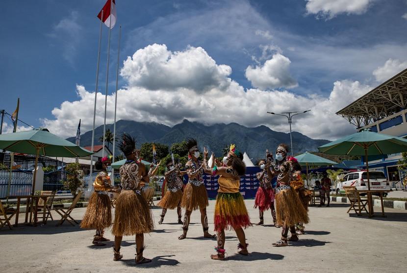 Para penari tradisional PON XX Papua 2021 melakukan tarian untuk menyambut kedatangan atlet si Stadion Barnabas Youwe, kabupaten Jayapura, Selasa (21/9).