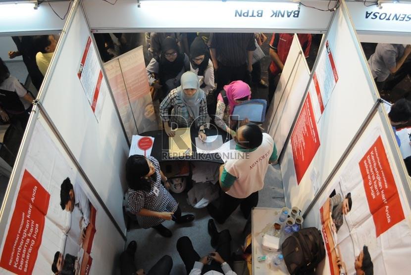 Para pencari kerja mencari informasi lowongan di stan-stan perusahaan peserta sebuah pameran bursa kerja di lapangan Tennis Indoor Senayan, Jakarta, Kamis (13/6).  (Republika/Aditya Pradana Putra)