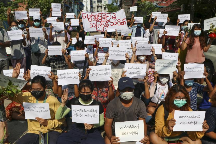 Para pengunjuk rasa memegang slogan yang mengutuk pemerintah militer saat mereka menandai festival Thingyan pada hari Selasa 13 April 2021 di Yangon, Myanmar. Aktivis mengorganisir boikot perayaan resmi Thingyan, Tahun Baru tradisional negara itu, biasanya waktu untuk reuni keluarga dan pesta pora.