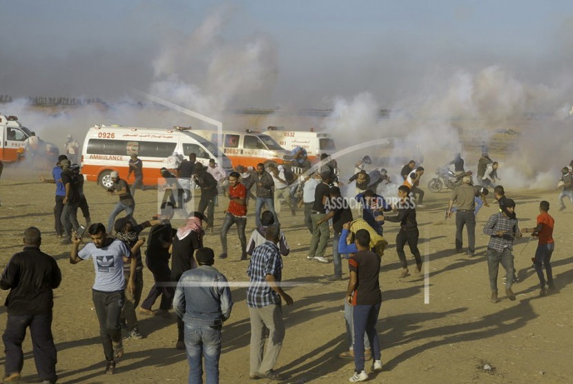 Palestinian civilians take cover from tear gas fired by Israeli forces during a protest at the Gaza Strip on Monday.