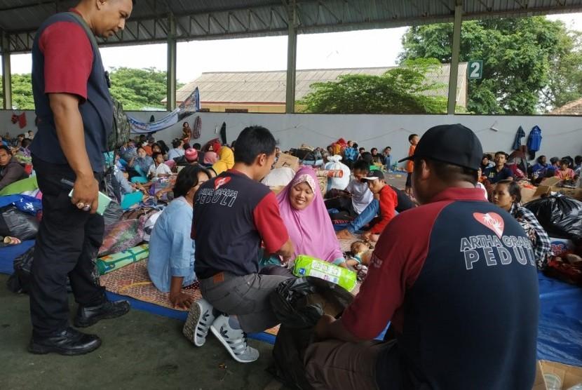 Para relawan Artha Graha Peduli (AGP) memberikan bantuan berupa keperluan bayi kepada seorang ibu di lapangan tenis Kalianda yang merupakan lokasi pengungsian untuk warga Pulau Sebesi dan Pulau Sebuku, Lampung Selatan, Kamis (27/12).