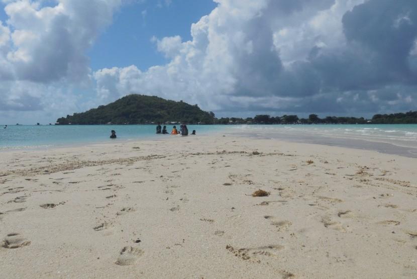Para wisatawan bermain pasir di Pulau Noko dengan latar belakang Pulau Gili di Bawean, Kabupaten Gresik.