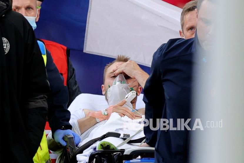 Paramedis menggunakan tandu untuk mengeluarkan Christian Eriksen dari lapangan setelah ia pingsan saat pertandingan grup B kejuaraan sepak bola Euro 2020 antara Denmark dan Finlandia di stadion Parken di Kopenhagen, Denmark, Sabtu (12/6).