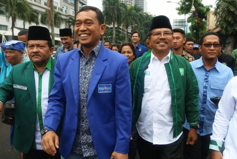 Pasangan bakal calon gubernur Sumut JR Saragih (kedua kiri) bersama bakal calon wakil gubernur Ance Selian (kedua kanan) berjalan menuju kantor KPU Sumut saat akan mendaftar, di Medan, Sumatera Utara, Selasa (9/1).