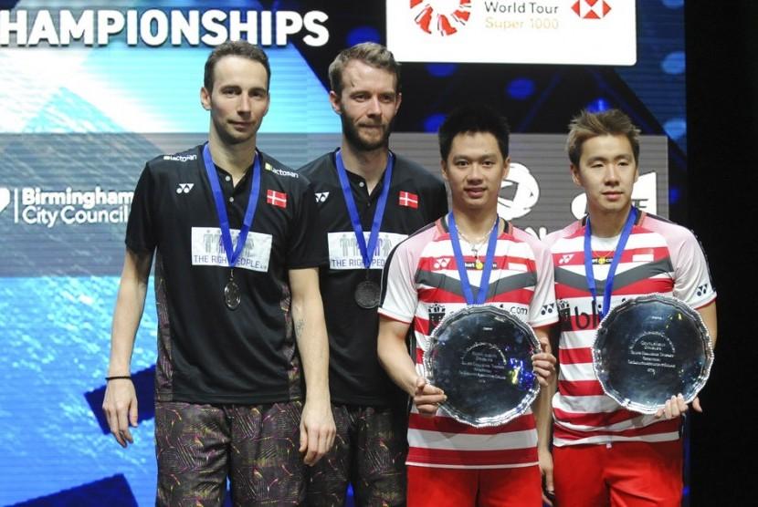 Pasangan ganda putra Indonesia, Marcus Fernaldi Gideon/Kevin Sanjaya Sukamuljo (kanan) di podium juara All England 2018, Ahad (18/3).