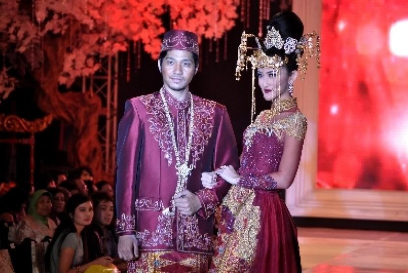 Pasangan pengantin dalam busana adat Betawi modern.