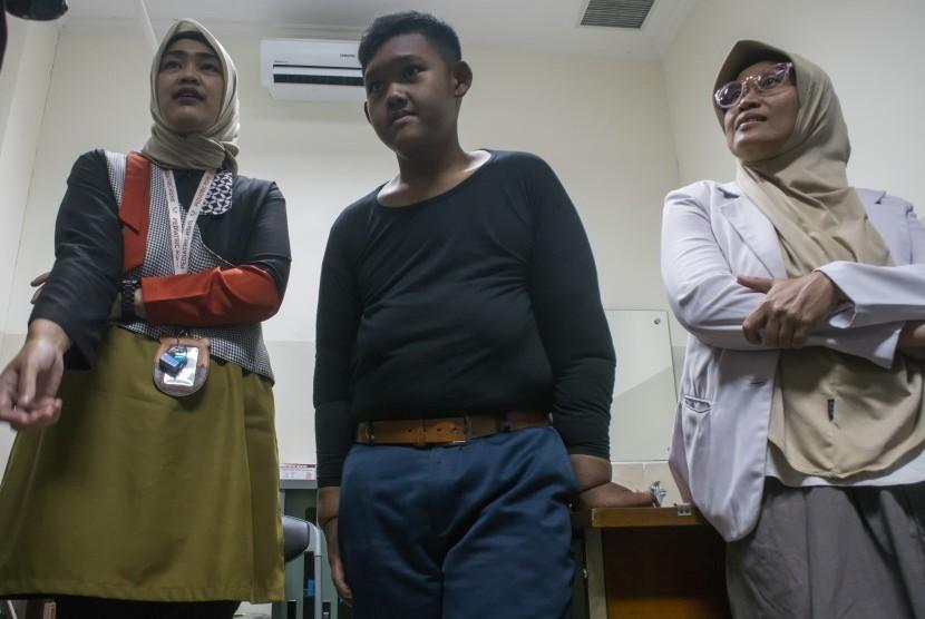 Pasien eks penderita obesitas Arya Permana (tengah) didampingi Dokter Spesialis Anak dan Gizi Anak bersiap melakukan pemeriksaan awal sebelum operasi bedah plastik di RSUP Hasan Sadikin, Bandung, Jawa Barat, Rabu (17/7/2019).