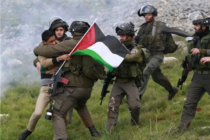 Pasukan keamanan Israel menahan seorang aktivis Palestina yang menentang pembangunan pemukiman Yahudi di Tepi Barat, Burin, Palestina.