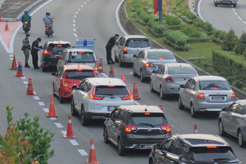 Pasukan operasi pematuhan dari Polisi Diraja Malaysia (PDRM) dengan didukung tentara melakukan blokade jalan (road block) di Jalan Kuching, Kuala Lumpur, Rabu (10/2/2021), dalam rangka membendung COVID-19. Sehari sebelumnya petugas gabungan sudah menahan 151 orang yang melakukan perjalanan melintas negeri/provinsi tanpa izin.