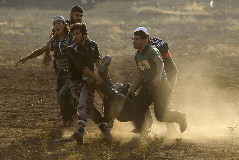 Pasukan Pembebasan Suriah (FSA) menggotong rekannya yang mengalami cedera dalam pertempuran melawan tentara Suriah loyalis Presiden Bashar Al Assad.