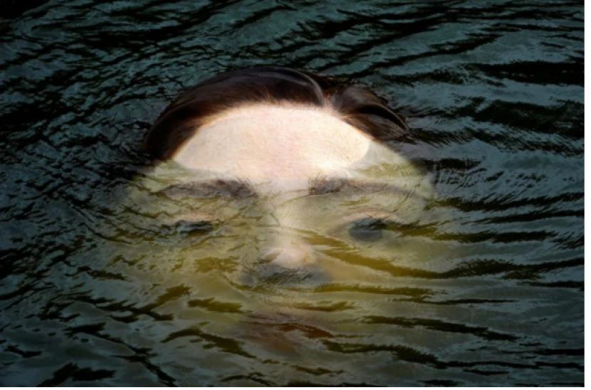 Patung wajah menyembul dari sungai di Spanyol.