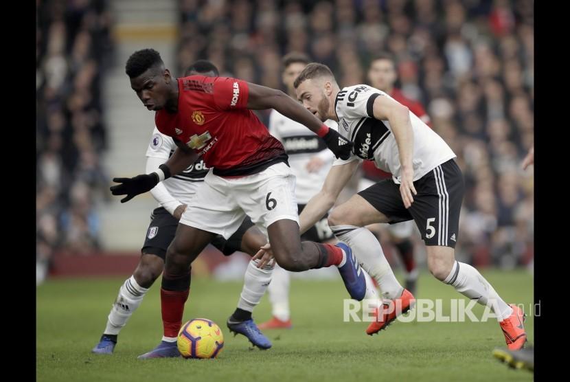 Paul Pogba berebut bola dengan Callum Chambers pada laga Liga Inggris antara Fulham melawan Manchester United di stadion Craven Cottage, London, Sabtu.