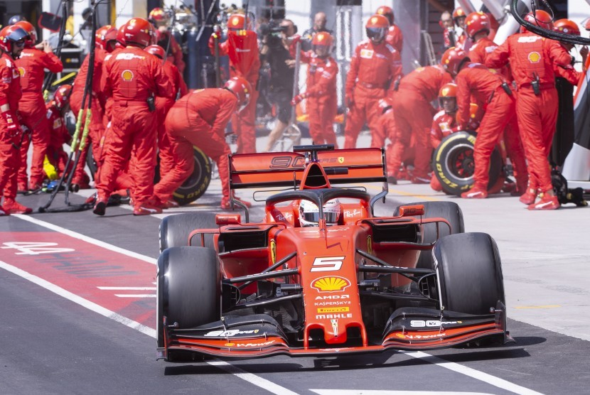 Pebalap Ferrari Sebastian Vettel meninggalkan pit stop di GP Kanada, Montreal, Ahad (9/6).