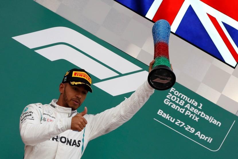 Pebalap Mercedes Lewis Hamilton mengangkat trofi setelah menjuarai Grand Prix F1 Azerbaijan di Sirkuit Baku, Azerbaijan.