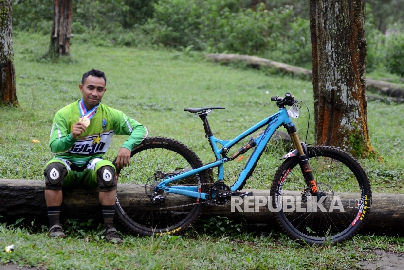 Pebalap sepeda gunung Jawa Barat Popo Ario Sejati menujukkan mendalinya usai final Downhill Individual Men Elite PON XIX di Cikole, Lembang, Jawa Barat, Rabu (20/9).