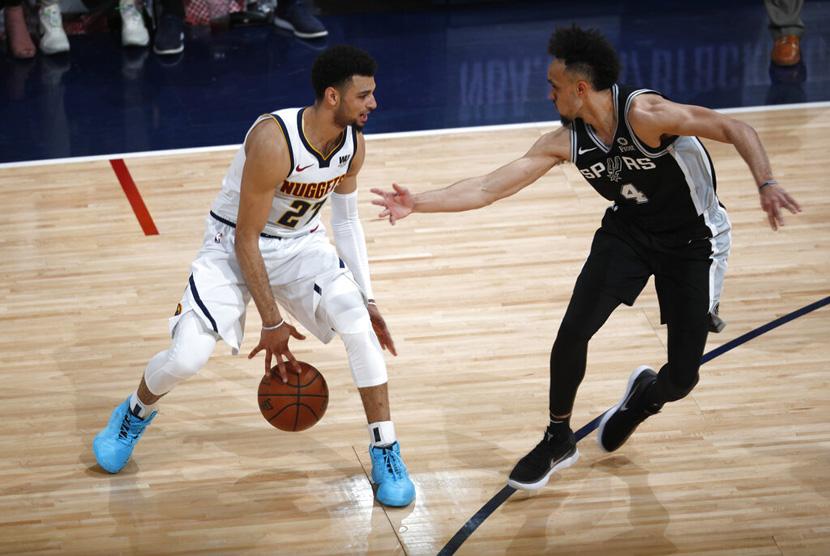 Pebasket Denver Nuggets Jamal Murray (kiri) mencoba melewati pebasket San Antonio Spurs Derrick White (kanan) di paruh kedua dari seri playoff bola basket NBA.