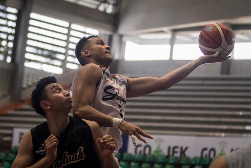 Pebasket Stapac Jakarta, Kaleb Ramot Gemilang (kanan) berusaha mencetak angka dengan dihadang pebasket Hangtuah, Steven Carsera (kiri) pada Turnamen Pramusim Indonesian Basketball League (IBL) di Gor Sritex Arena, Solo, Jawa Tengah, Rabu (17/10/2018). Pada pertandingan tersebut Stapac Jakarta menang dengan skor 68-59.