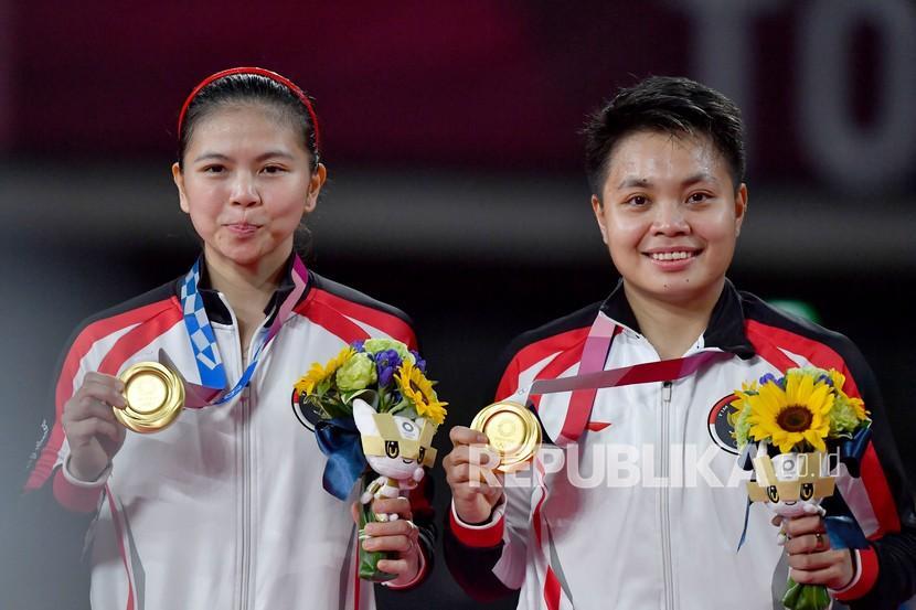 Pebulutangkis ganda Putri Indonesia Greysia Pollii (kiri) dan Apriyani Rahayu memperlihatkan medali emas yang berhasil mereka raih untuk nomor bulutangkis ganda putri Olimpiade Tokyo 2020 di Musashino Forest Sport Plaza, Tokyo, Jepang, Senin (2/8/2021). Greysia Pollii/Apriyani Rahayu berhasil meraih medal emasi setelah mengalahkan Chen/Jia Yi Fan dua set langsung. 21-19 dan 21-15.