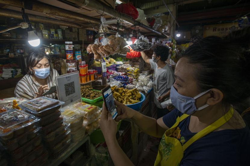 Pedagang melayani pembeli dalam melakukan pembayaran non tunai di salah satu los sembako di Pasar Mayestik, Kebayoran Baru, Jakarta, Selasa (11/5/2021). Berdasarkan data Bank Indonesia yang dirilis April 2021, nilai transaksi uang elektronik di Indonesia mencapai Rp21,4 triliun pada Maret 2021 atau tumbuh 42,46 persen (year on year) karena dipicu peningkatan akseptasi dan preferensi masyarakat untuk berbelanja daring, meluasnya pembayaran digital dan akselerasi