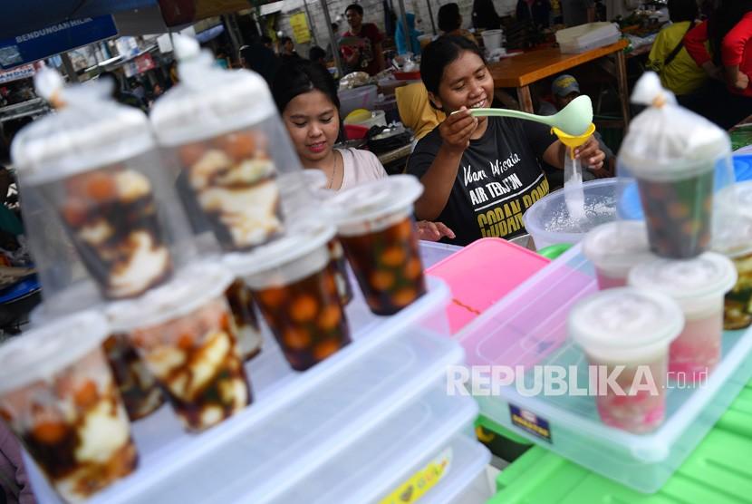 Pedagang membungkus minuman untuk dijual di Pasar Takjil Benhil, Jakarta, Senin (6/5/2019).
