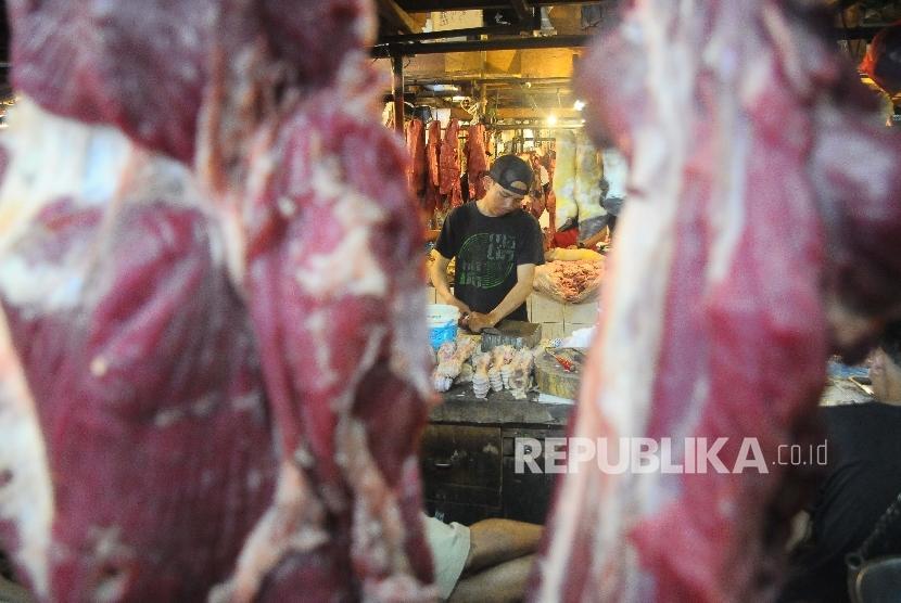 Pedagang memotong daging sapi yang di jual di pasar (ilustrasi)