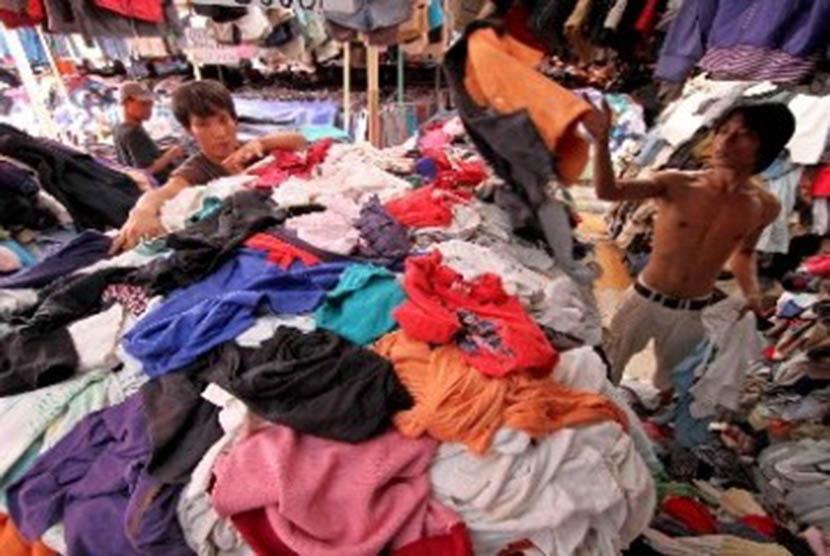 Pedagang menata pakaian bekas impor yang dijual di arena pasar malam. (ilustrasi).