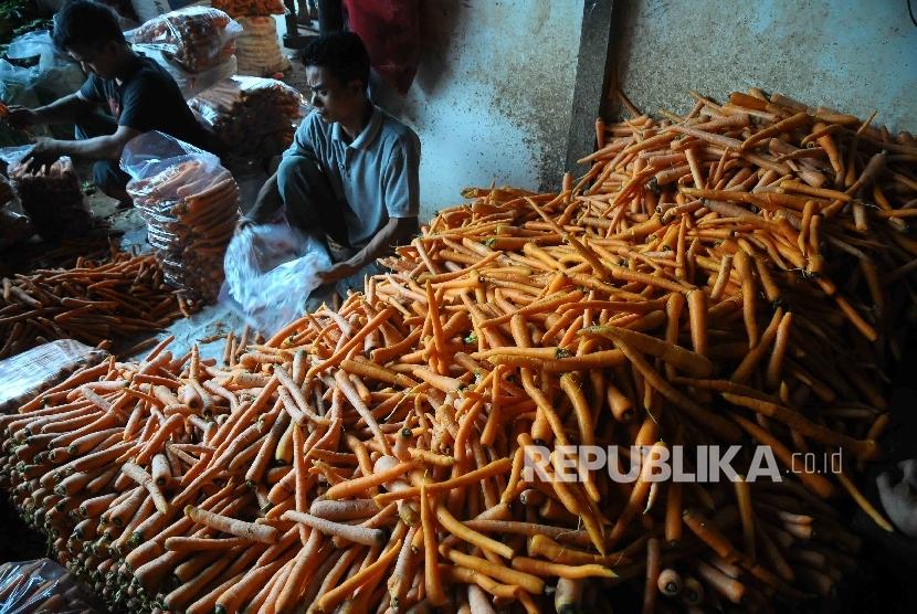 Pedagang menata wortel.