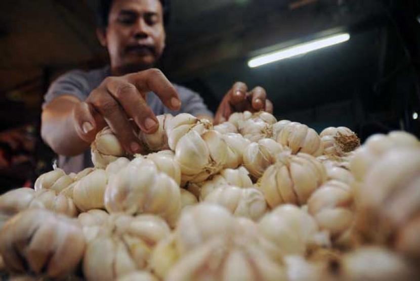 Pedagang mengambil bawang putih impor dari Cina untuk ditimbang di pasar tradisional. ilustrasi