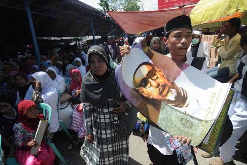 Pedagang menjajakan poster Guru Tua (Habib Sayyid Idrus Bin Salim Al-Djufrie) saat perayaan Haul (peringatan hari wafat) ke-47 tahun Guru Tua yang dihadiri ribuan umat muslim dari seluruh Indonesia di Palu, Sulawesi Tengah, Selasa (28/7).