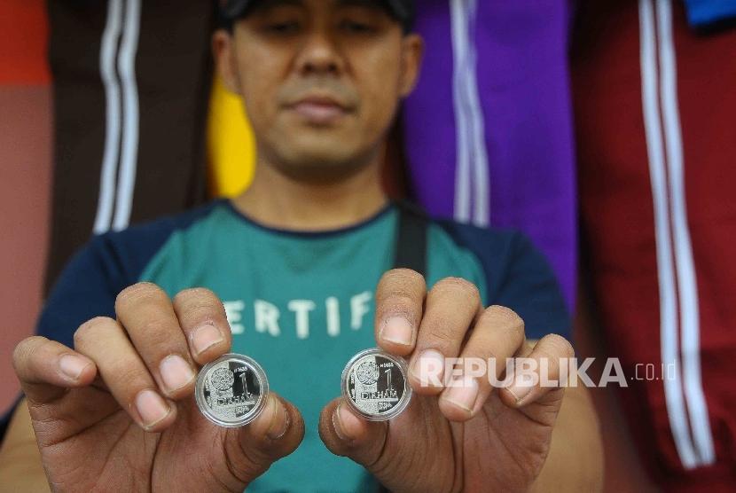 Pedagang menunjukan dirham di Pasar Muamalah, Kota Depok, Jawa Barat, Ahad (18/12).