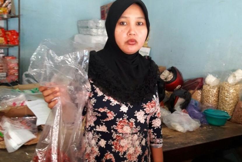 Pedagang pasar Baru Indramayu, Warinih, menunjukkan cabai impor yang dijualnya kepada para pembeli, Jumat (17/2).