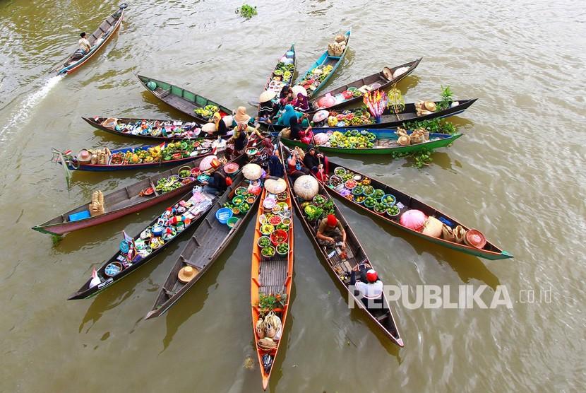 Pedagang Pasar Terapung melakukan atraksi Jukung (perahu) di Desa Lok Baintan, Kabupaten Banjar, Kalimantan Selatan.