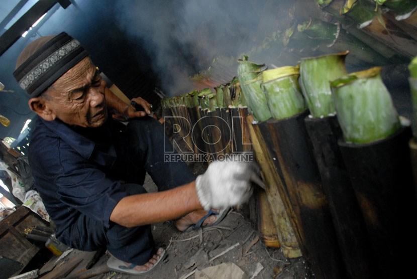 Pria ini tengah memasak Lemang untuk dijual demi menafkahi istri dan anak-anaknya (Ilustrasi)