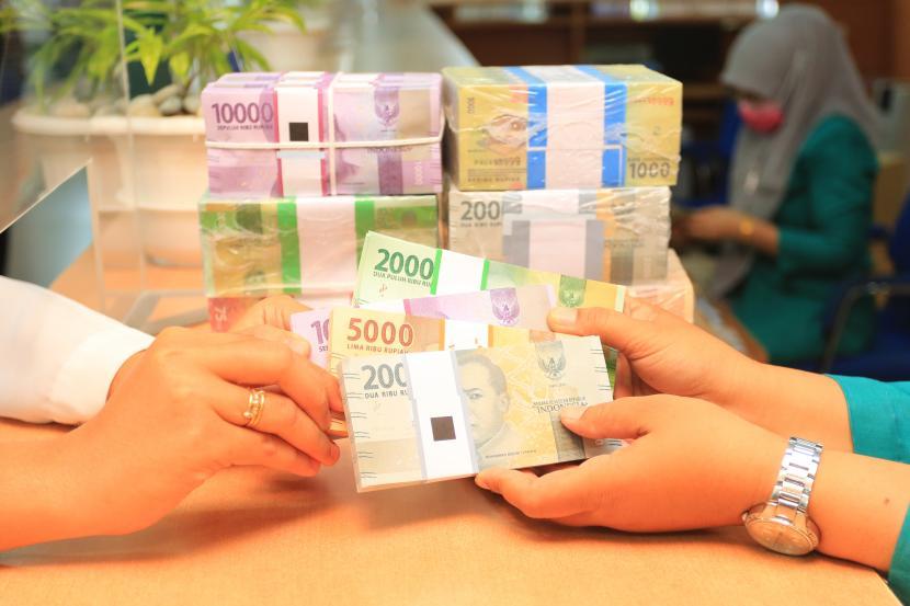 Pegawai bank melayani warga untuk menukarkan uang pecahan kecil.