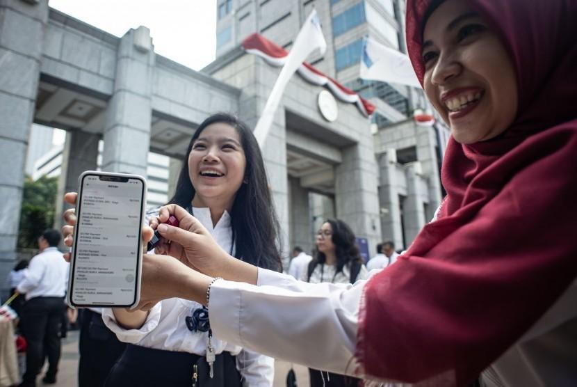 Pegawai Bank Indonesia (BI) menunjukkan bukti transaksi menggunakan peluncuran QR Code Indonesian Standard (QRIS) di halaman Gedung Bank Indonesia, Jakarta, Sabtu (17/8/2019).