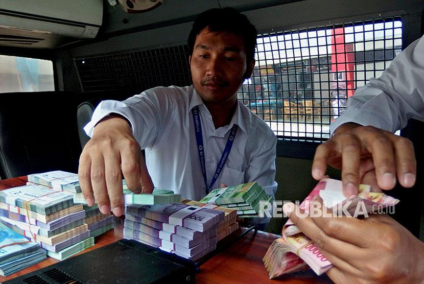Pegawai Bank Indonesia menyiapkan uang baru di loket mobil kas keliling Bank Indonesia, saat pembukaan layanan penukaran uang di Semarang, Jawa Tengah, Senin (21/5).
