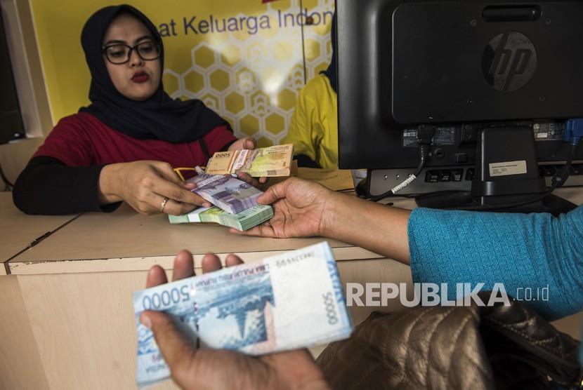 Pegawai bank melayani warga yang menukarkan uang