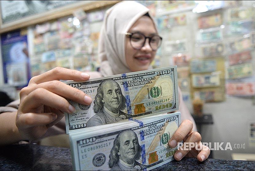 Pegawai menghitung mata uang dolar AS di jasa penukaran mata uang, Jakarta, Ahad (8/4). Bank Indonesia (BI) mencatat posisi cadangan devisa Indonesia pada akhir April 2021 mencapai 138,8 miliar dolar AS.